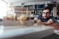 Designer thinking about new architectural ideas. Young architect working on house model. Male designer at his workdesk thinking about new architectural ideas stock photo