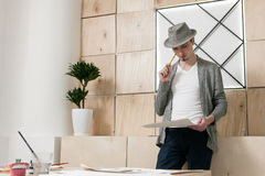 Designer thoughtfuly stands looking at paper. Young man considers on work results of designer sketch royalty free stock photo