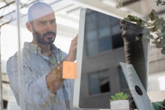 Designer using computer in studio seen through glass Royalty Free Stock Image