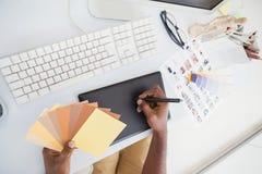 Designer using digitizer and colour wheel Royalty Free Stock Photos