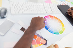 Designer using graphics tablet and colour wheel. In the office Stock Image