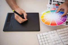 Designer using graphics tablet and colour wheel Royalty Free Stock Images