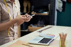 Designer using smartphone at work. Close-up of male designer sitting at the table in front of laptop and typing a message on his smartphone stock photo