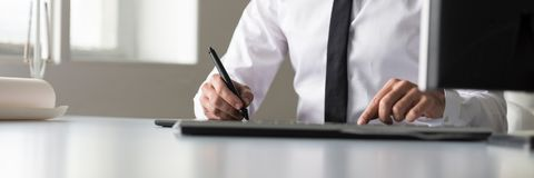 Designer using a tablet and stylus pen in wide panorama low angl Stock Image