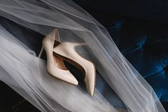 Designer wedding beige bride shoes on an expensive velour sofa, tulle or veil. Women`s new modern fashion high-heeled shoes, royalty free stock photography