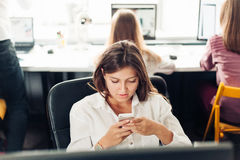 Designer woman using phone in the office Stock Photos