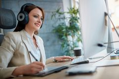 Designer woman wearing headphones and working in design studio. Casual designer woman wearing headphones and working in design studio stock photos