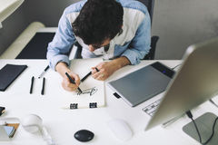 Designer at work in office. Man drawing in note pad stock photos