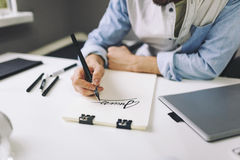 Designer at work in office. Man drawing in note pad stock image