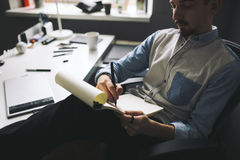 Designer at work in office. Man drawing in note pad royalty free stock images