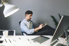 Designer at work in office. Man drawing in note pad royalty free stock photo