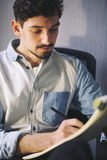 Designer at work in office. Man drawing in note pad stock photography