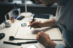 Designer at work in office. Man drawing in note pad royalty free stock photography