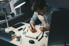 Designer at work in office. Man drawing in note pad royalty free stock photos