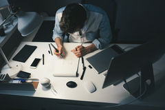 Designer at work in office. Man drawing in note pad stock photo