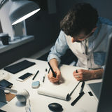 Designer at work in office. Man drawing in note pad stock images