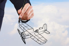 Designer at work. Person hand drawing old airplane on sky background Stock Images
