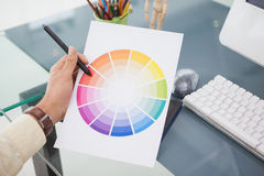 Designer working at desk using a colour wheel Stock Photo