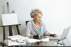 Designer working on graphics tablet. Portrait of smiling designer working on graphics tablet against wooden easel with clean paper and art supplies in room Stock Photo