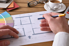 Designer working on an interior design project elevated. Designer working on an interior design project on wood table with a house plan, tools and samples Stock Images