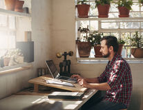 Designer working on laptop in his creative office space Stock Photography