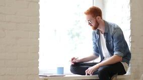 Designer Working on New Design, Sitting in Window, w/ Red Hars and Beard. Creative designer , businessman stock video