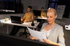 Designer working with papers at night office stock photos
