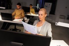Designer working with papers at night office stock photo