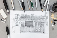 Designer workplace with freehand sketch of wall unit and various drawing tools Royalty Free Stock Image
