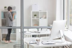 Office environment. Designer workplace in office near transparent noteboard and accountant working behind it Stock Photo