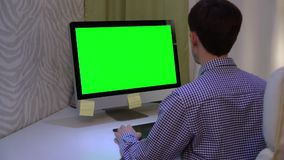 The designer works on a graphic tablet at the PC with chroma key green screen. stock video
