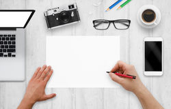 Designer writes on a blank paper. Top view of work desk with computer, phone, camera, glasses, coffee.  royalty free stock photography