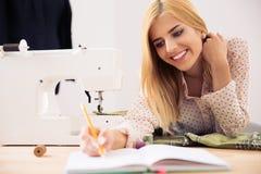 Designer writing notes in workshop Stock Images