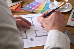 Designer writing on the plan of an interior design project. Designer working on an interior design project on wood table with a house plan, tools and samples stock image