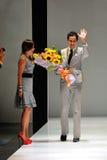 Designer Zac Posen, das Blumenstrauß von Blumen nach seinem Show bei Audi Fashion Festival 2012 empfängt Stockbild
