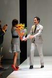 Designer Zac Posen, das Blumenstrauß von Blumen nach seinem Show bei Audi Fashion Festival 2012 empfängt Lizenzfreies Stockfoto