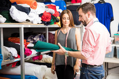 Designers choosing the right fabric. Attractive couple of fashion designers trying to choose the right fabric for their new project Stock Image