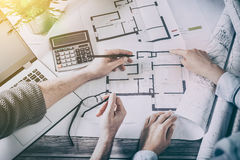 Designers discuss the sketches inside the house. Royalty Free Stock Image