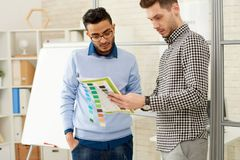 Designers Discussing Color Palette. Portrait of two young men, one of them Middle-Eastern, discussing color palette for pamphlet design standing in modern office stock photography