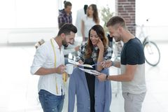 Designers discussing the design of the male suit. In the Studio Stock Photos