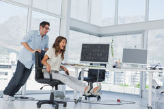 Designers having fun with a swivel chair. In their office royalty free stock images