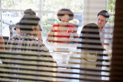 Designers Having Meeting Viewed Through Window Royalty Free Stock Images