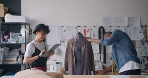 Designers measuring clothing on dummy and using tablet to put in measurements. People designers African American guy and Caucasian lady are measuring clothing on stock video