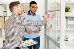 Designers Planning Publishing in Office. Portrait of two young entrepreneurs sticking post it notes on glass wall while planning startup project in modern office Royalty Free Stock Images