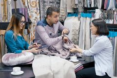 Designers, sellers of fabrics working in the showroom, choosing fabrics in the new interior.  stock photography