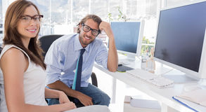 Designers sitting at their desk and smiling at camera Stock Images