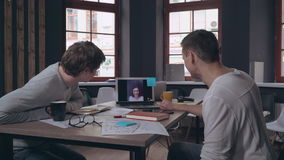 Designers use app for remote meeting. Coworkers have video call conference with friend. Two men sitting in the office have funny conversation with woman stock video