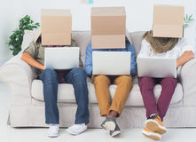 Designers working on laptops with boxes over their head Stock Photo