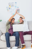 Designers working together with a laptop then high fiving Royalty Free Stock Image