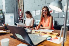 Designers workspace. Two female artists drawing decorative elements sitting at desk in creative studio royalty free stock photography